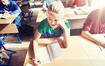 Students sitting at their desks writing in a notebook