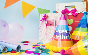 Table with party hat, gift bag, wrapping paper, balloons and confetti.
