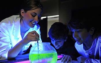 Mad Scientist pouring liquid that turns green with the use of a black light into a bowl of water with 2 kids looking on.